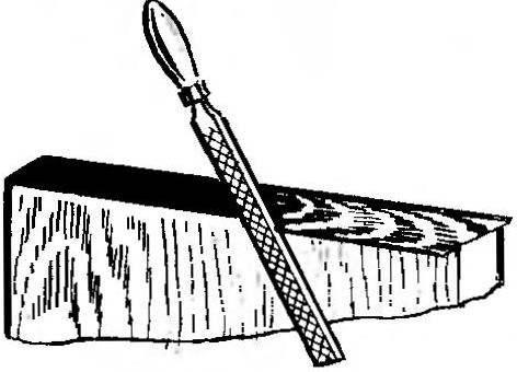 Рис. 3. Обработка кромки плиты напильником