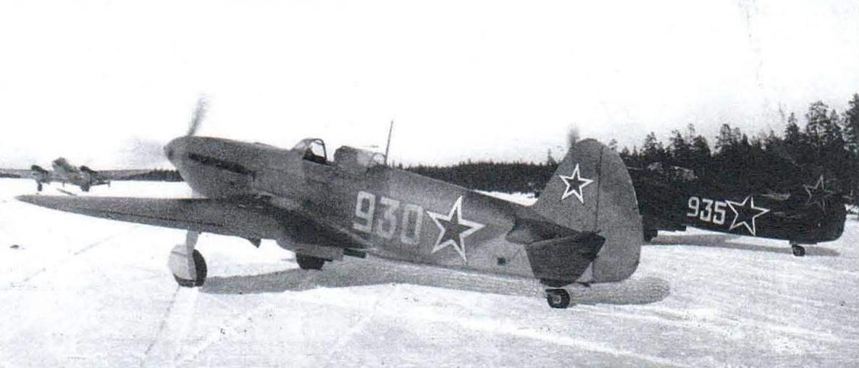 Камуфляж истребителя Як-9 идеально совпадает со стандартной схемой 1943 г. (машины уже не покрывались зимой белой краской). Самолёт на заднем плане явно побывал в ремонте и получил увеличенные опознавательные знаки. Трёхзначные бортовые номера на обоих истребителях нанесены в полку и информируют о принадлежности машин к подразделению. Зима 1944/1945 г., 3 воздушная армия.