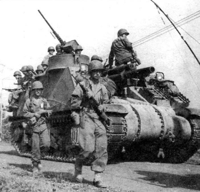 САУ М7 выдвигается на передний край обороны с пехотой на борту. Филиппины, остров Лусон. Март 1945 г.
