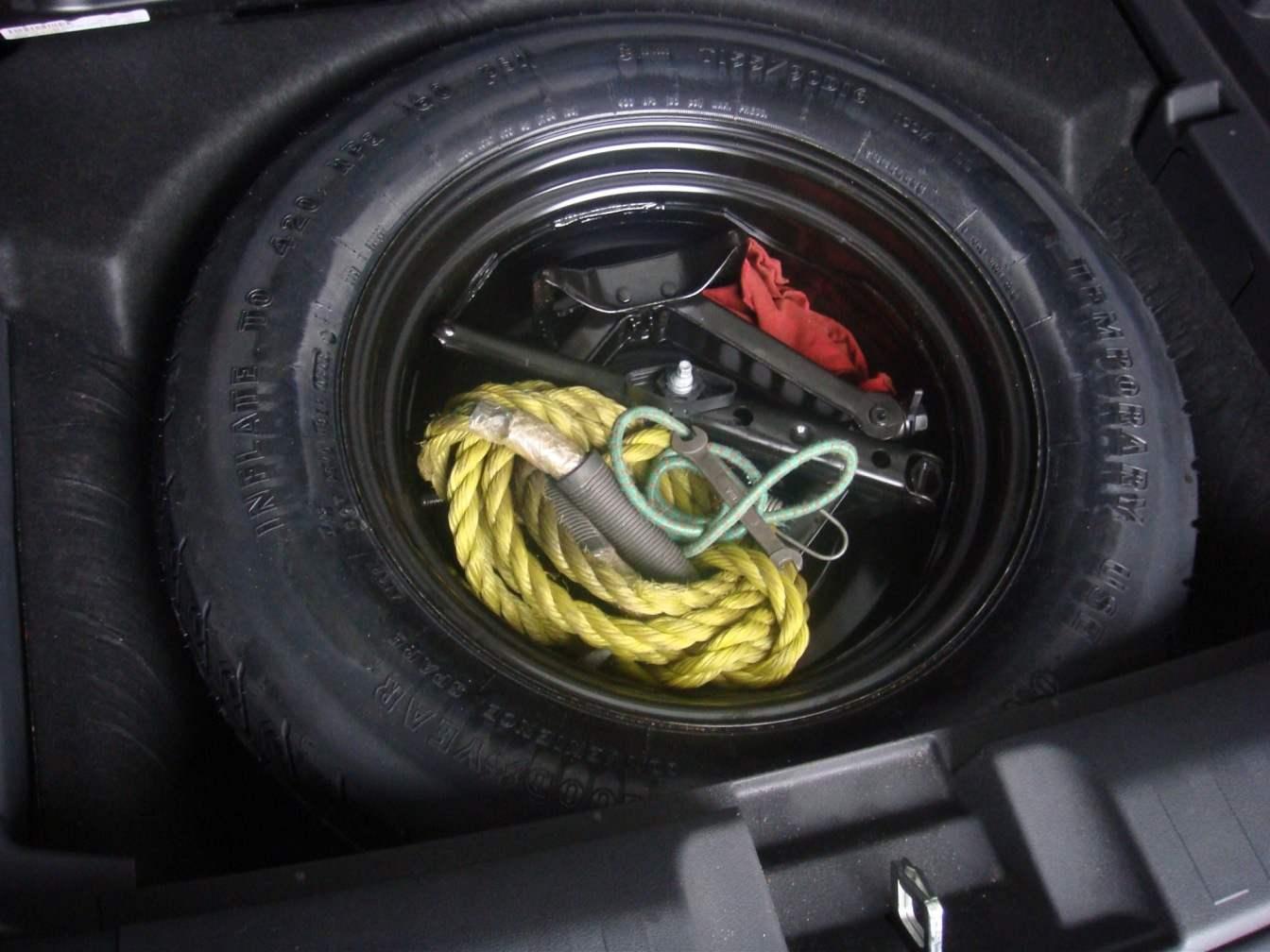 Запасное колесо-докатка располагается под жестким полом багажника