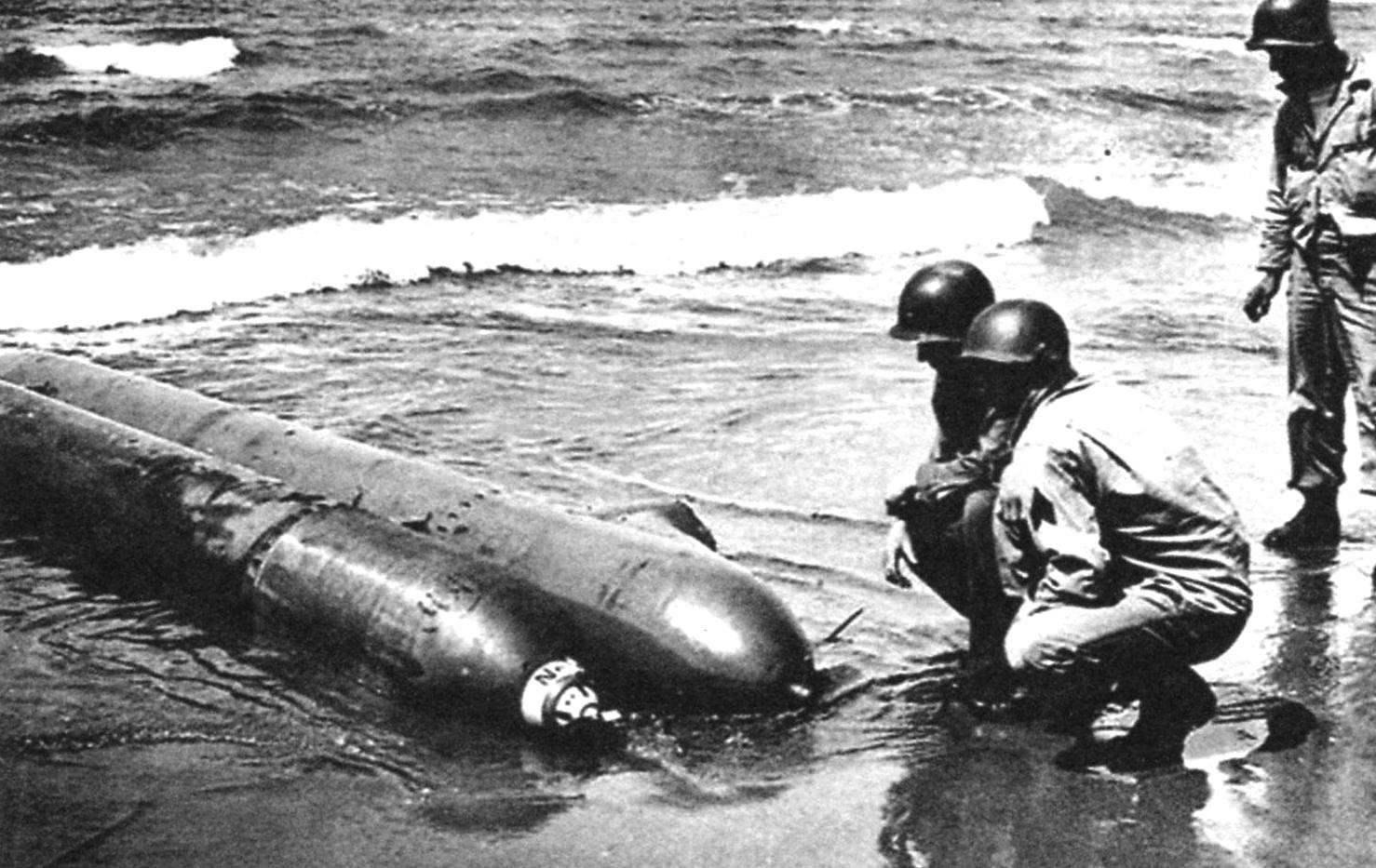Американские солдаты рассматривают торпеду Neger, выброшенную на берег близ Анцио. У этого снимка есть противоречивые толкования: немцы утверждают, что это торпеда погибшего пилота (все остальные были уничтожены), американцы пишут, что торпеду бросили по халатности, не сумев спустить на глубокую воду