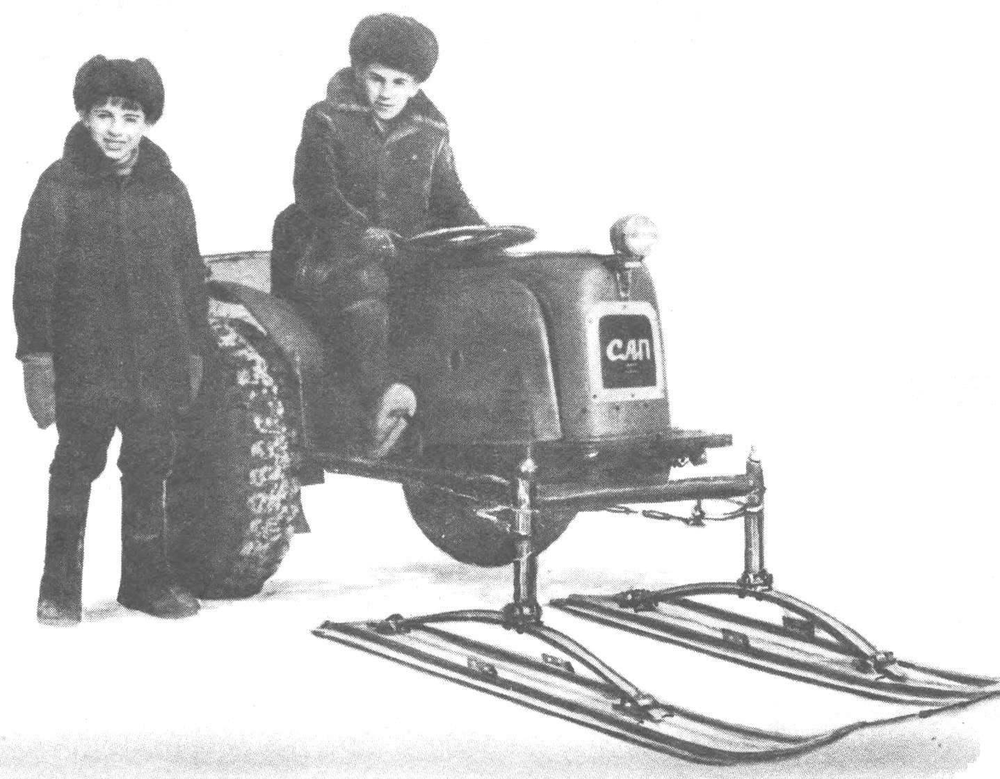 Трактор-малыш,сконструированный школьниками Сережей и Андреем Павловыми, может не только буксировать двухколесный прицеп, но и пахать, боронить, культивировать почву, поливать пришкольный участок. Зимой же передние колеса заменяются лыжами — и трактор превращается в снегоход.