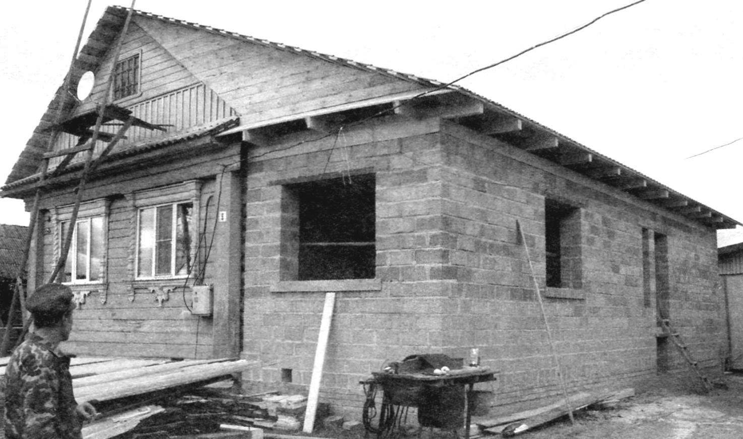 Old wooden house and the new porch of aggregate concrete blocks under a new common roof