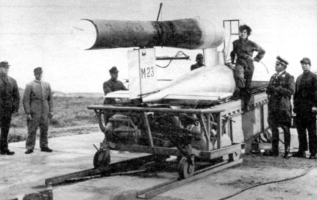 Ханна Рейтч у экспериментального снаряда «Райхенберг I», с бортовым номером М23. (М значит - экспериментальный). Снаряд установлен на катапульте, предназначенной для запуска «Фау-1». Судя по обгоревшей грубе двигателя, эта машина уже бывала в полёте