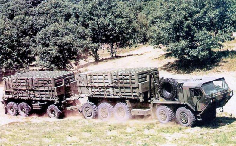 В систему РСЗО MLRS входят обслуживающие транспортно-заряжающие машины М-1075 (10x10) с прицепами М989. На каждом таком поезде перевозят 48 реактивных снарядов боекомплекта