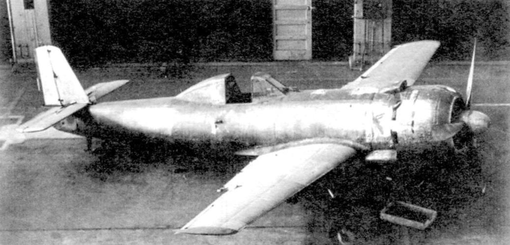 Ки-115 перед сборочным цехом. Цвет самолёта - серебристый. Опознавательных знаков на крыльях незаметно. Шасси - жёсткое