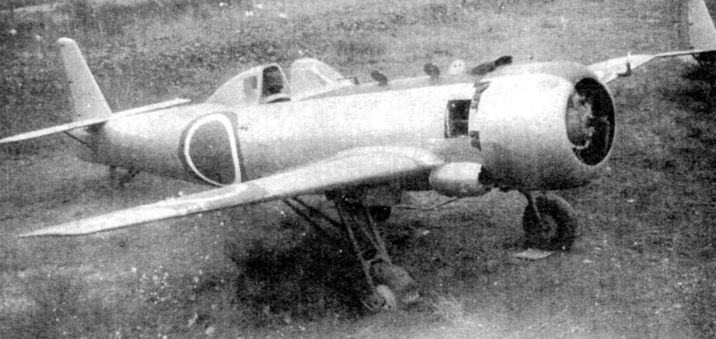 Самолёт Ки-115, окрашенный серебристой краской. Шасси жёсткое. На левом крыле - «ломаная» трубка ПВД. Перед кабиной - чёрная антибликовая полоса и открытые лючки. Изображение «солнца» на фюзеляже и крыльях - с белой обводкой на зелёном пятне