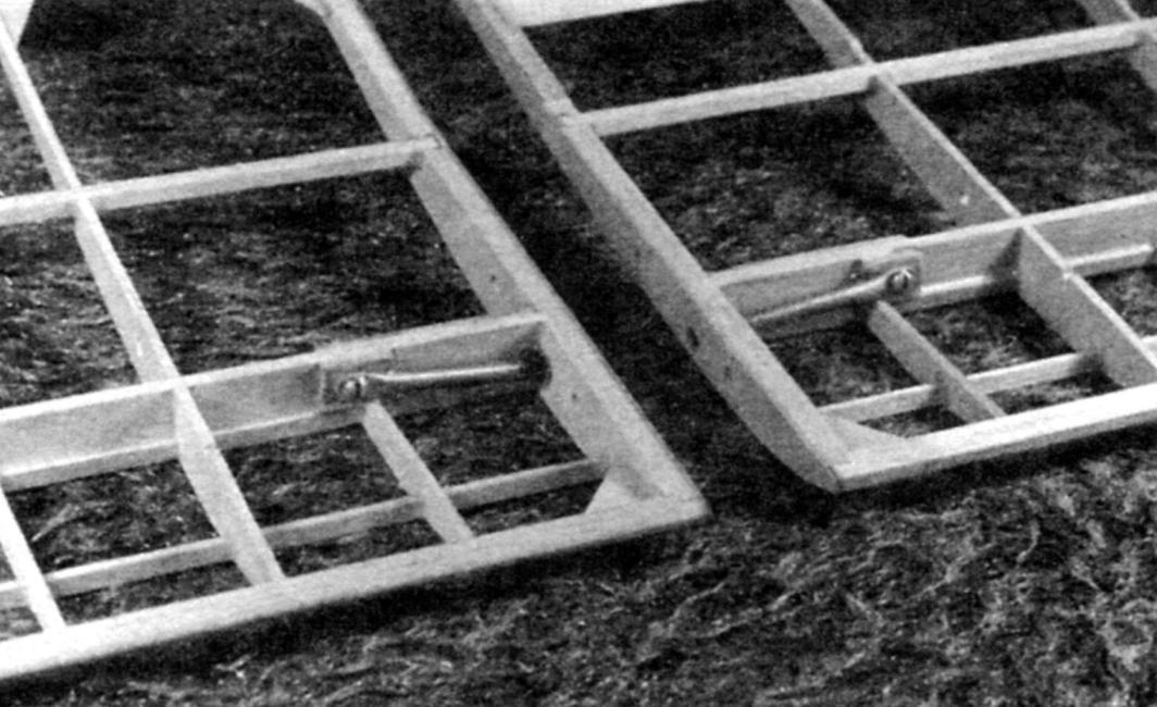 Разъём крыла, вид спереди. К стенке лонжерона сплюснутые концы трубчатых «пеналов» крепятся винтами М3 через фанерные прокладки. Входные части трубок зачищены, обмотаны тонкими нитками и заклеены в корневых нервюрах. Все стыки пролиты эпоксидной смолой. Корневые нервюры имеют по паре сквозных отверстий для прохода воздуха