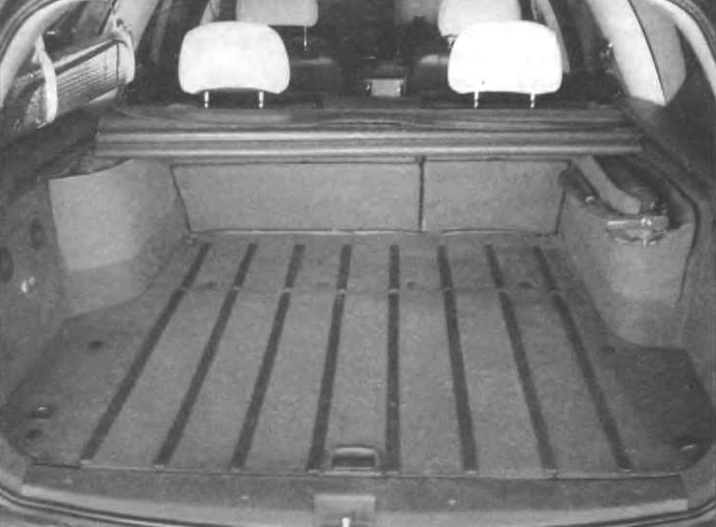 Вид багажного отделения с рундуками на колесных арках, заполненными необходимыми в дороге мелкими вещами