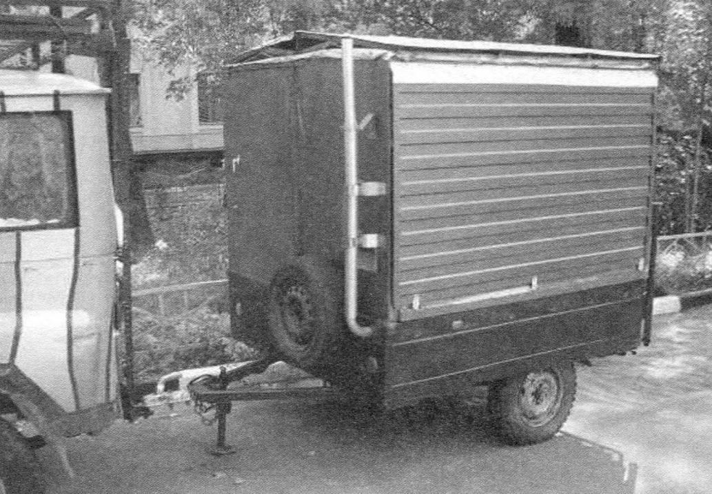 Домик-прицеп после хранения подцепляется к автомобилю-тягачу и подготавливается к автопутешествию (двускатная крыша находится еще на будке и не убрана передняя плавнорегулируемая опора-домкрат)