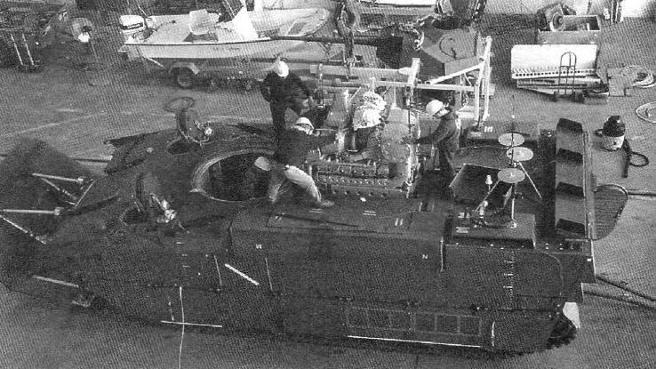 Корпус EFV в сборочном цехе. В его передней части видны отверстия люков механика-водителя, командира десанта и в центре-башенное. Сборщики опускают на место дизельный двигатель