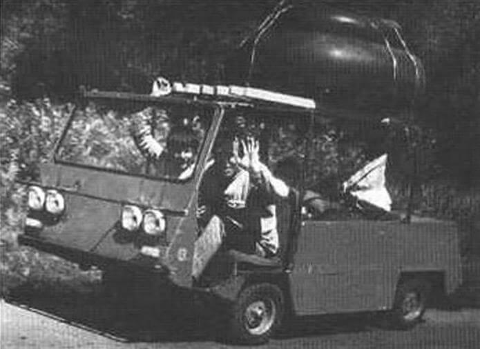 Микроавтомобиль из запчастей от инвалидной коляски С3Д. Двигатель - «ИЖ-П3», редуктор с передачей заднего хода. На багажнике - камеры для купания. За рулем - педагог В.Ф. Важен ни. Рядом - член кружка «Малогабаритной техники» Володя Соснин