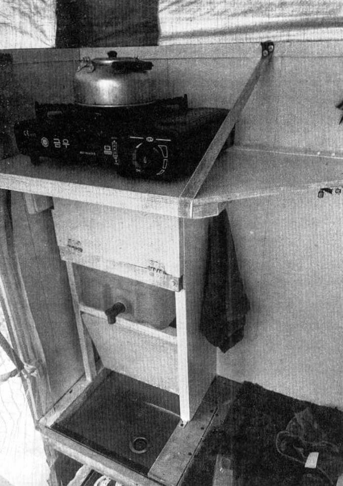 Кухня расположена слева от входа и имеет вертикальную компоновку. Сверху на откидной полке находится газовая плита, ниже 28-литровый бак для воды, под ней раковина, слив - по шлангу на улицу