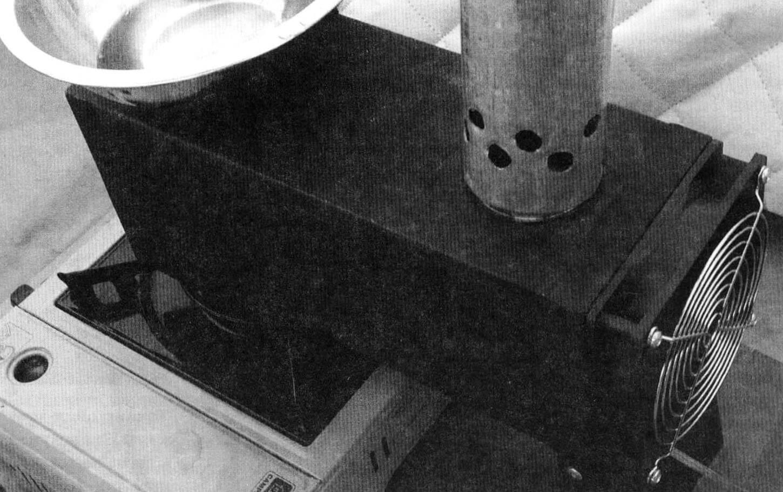 Обогреватель с теплообменником, установленный на газовую плиту: вентилятор выдувает горячий воздух, а угарный газ выводится через дымоход наружу