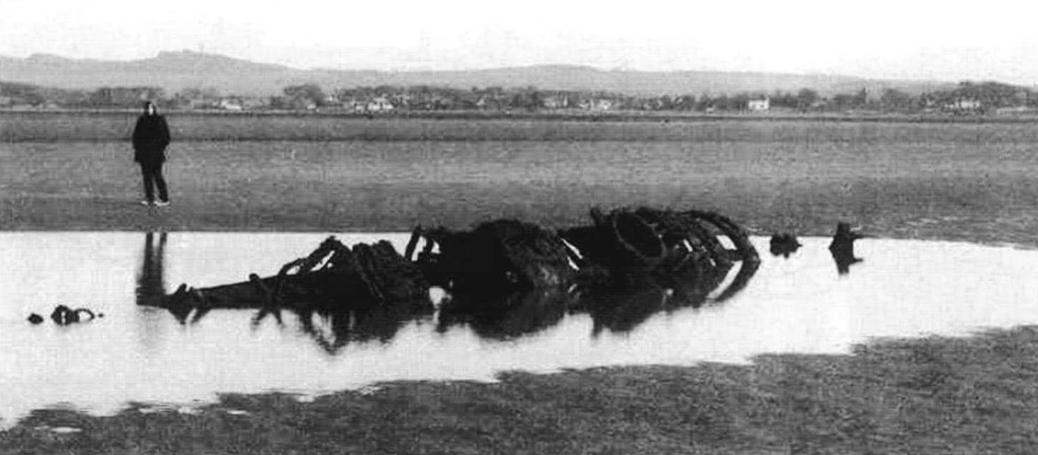 Останки одной из двух мини-субмарин типа «ХТ» на пляже в заливе Аберлэди в Шотландии по состоянию на 2008 год. Нос слева, корма справа. Можно видеть остатки отдельных отсеков: «сухого-мокрого» с «мокрым» люком для водолаза, рубку и второй люк. В 1946 году две лодки этого типа были закреплены бетонным «якорем» и использовались в качестве мишеней для авиации