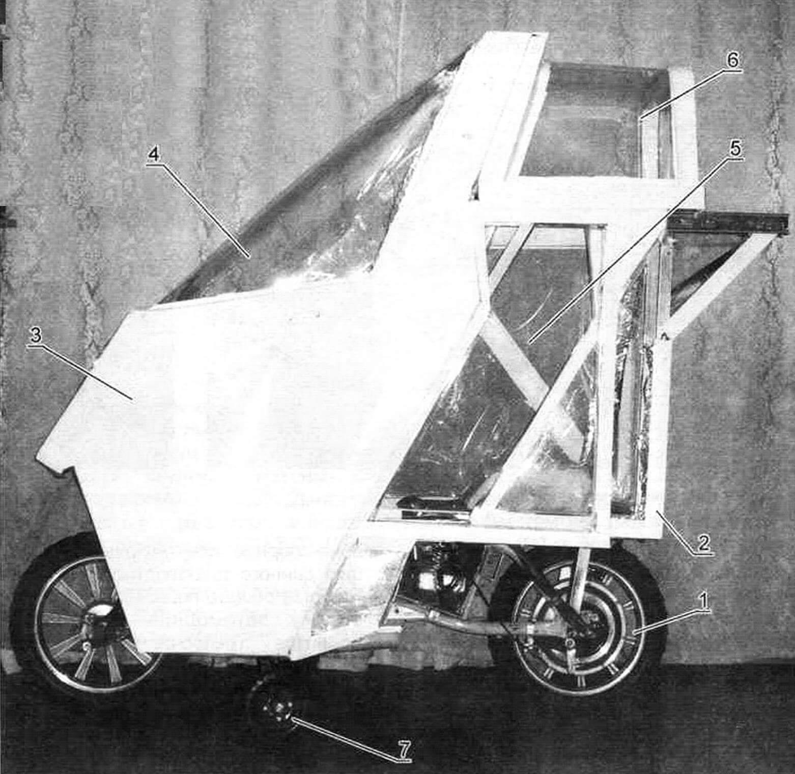 Ходовая модель мотомобиля базируется на детском электровелосипеде (1), на котором смонтирован легкий каркас (2), несущий на себе передний обтекатель из поликарбоната (3) с лобовым стеклом (4), сдвижные двери (5) и «фонарь» (6). Внизу установлены убирающиеся опорные колеса (7)