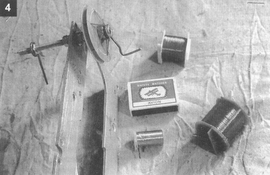 Намоточное устройство на рейки из фанеры толщиной 8 мм. Справа: приемный вал с разборным каркасом (видны нитки для перевязки бухты провода). Гайка М6х1 - счетчик витков. При каждом обороте гайки с грузиком перемещается по валу-винту вправо до упора (в моем случае - это 42 мм). Значит, намотано 42 витка. На чистом листе бумаги ставится «крестик»...