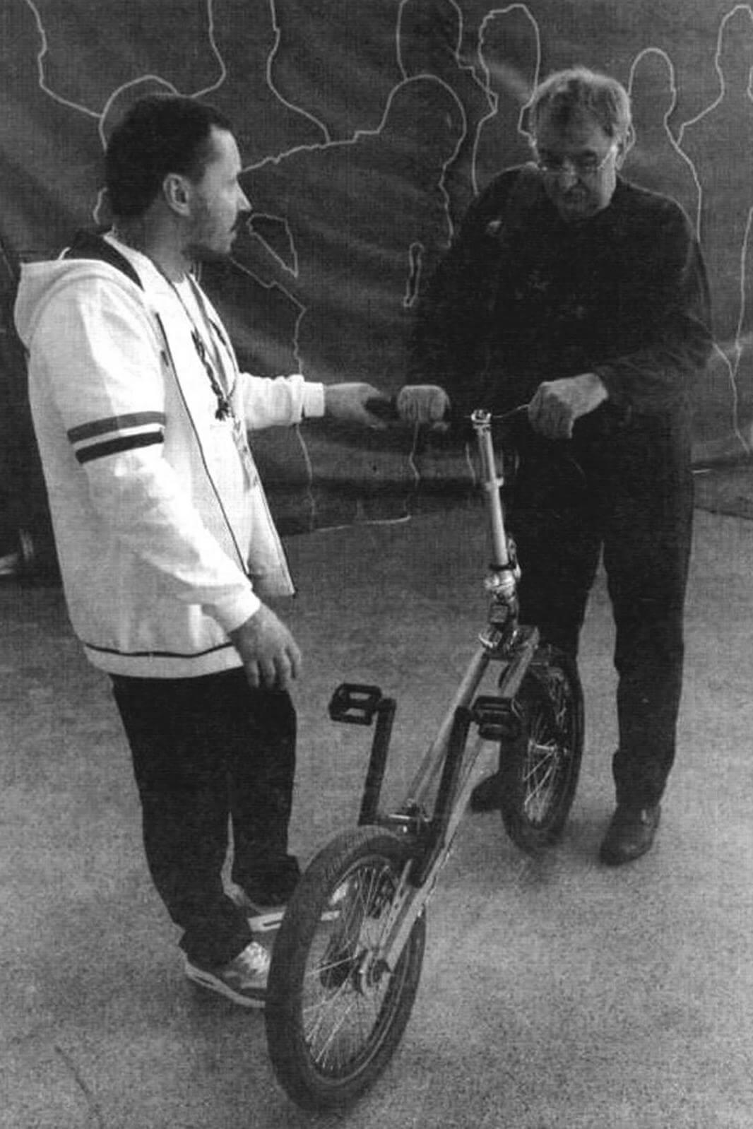 Сергей Федотов (на фото слева) объясняет очередному заинтересованному посетителю выставки, как работает трансмиссия его необычного транспортного средства UniCab Bike. Чтобы привести его в движение, нужно не крутить педали, а нажимать на них, имитируя подъем по лестнице