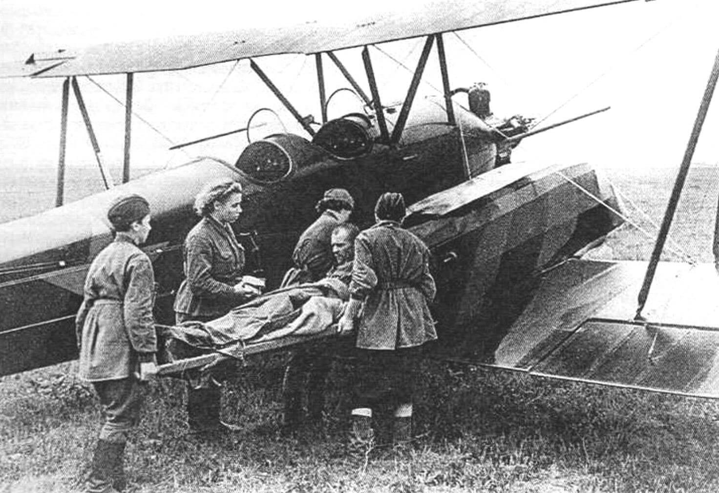 Девушки-медики загружают раненого бойца в У-2, оборудованный санитарными кассетами Бакшаева (1942 год)