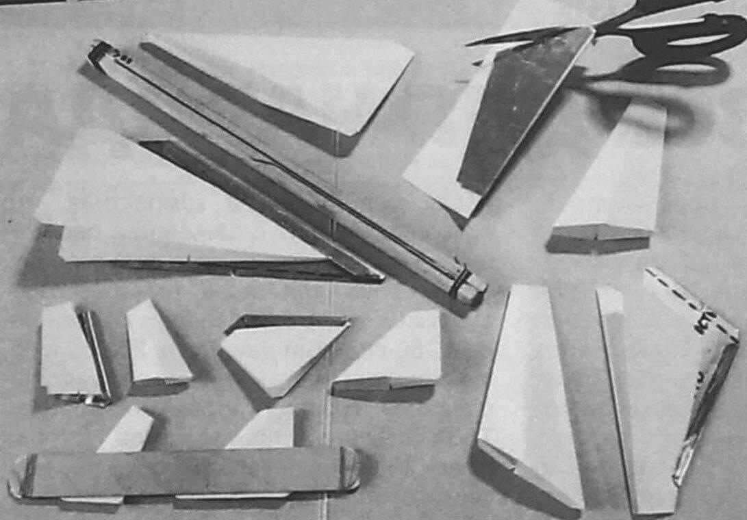 Процесс вырезания деталей моделей с помощью жестяных шаблонов. В качестве прижимов при склеивании используются деревянные линейки, стянутые резинками