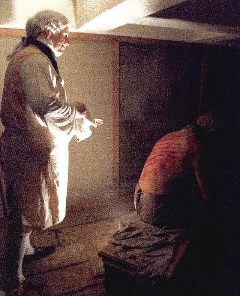 Лекарь обрабатывает спину подвегшегося порке матроса